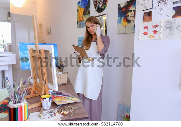 Lovely Female Painter Orders Things to Draw or Picture Frames , Clarifies Meeting With Students For Master Class, Communicates With Clients About Sale of Paintings. Woman With Long Light Brown Hair