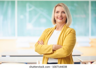 Lovely female teacher looking at camera and smiling while standing with arms crossed in the classroom before the chalkboard.
