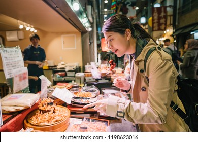 lovely female tourist standing in front of the vendor in the market and pointing to the Japanese street food. the shop owner is smiling at her in the background. Joyful backpacker travel in Japan.