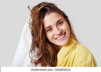 Lovely female with wet hair, takes shower, dries head with towel, being pleased after taking bath, dressed in yellow bathrobe, poses against white background, has cheerful expression