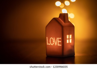 Lovely festive candle light house with LOVE inscription and window. Warm, pleasant and soft light. Love, comfort, quietness. Peaceful moment with your loved ones. Family gathering, festive season.