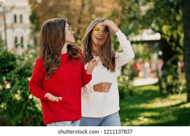 lovely friendly girls walking outdoor and talking with eath other with true good emotions. Outdoor portrait of two sisters enjoying weather on street background.
