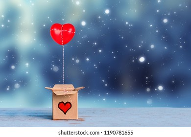 lovely gift box with red heart on blue winter background