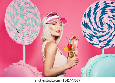 Lovely girl with blonde hair wearing top and pink cap standing with huge sweet lollypops at pink background, candy lover, drinking lemonade, close up portrait.