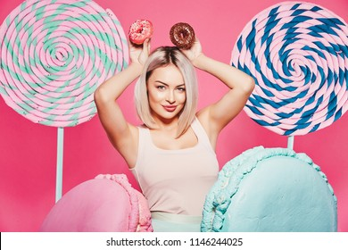 Lovely girl with  blonde hair wearing top and pink cap standing with huge sweet lollypops at pink studio background, candy lover, posing with donuts, sexy model.