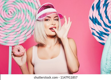 Lovely girl with  blonde hair wearing top and pink cap standing with huge sweet lollypops at pink studio background, candy lover, posing with donuts, sexy.