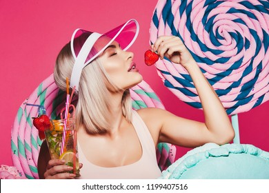 Lovely girl with blonde hair wearing top and pink cap standing with huge sweet lollypops at pink background, candy lover, drinking lemonade, close up.