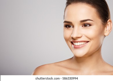 Lovely girl with brown hair, clean fresh skin and naked shoulders posing at gray studio background, a model with light nude make-up, perfect teeth, shining smile.
