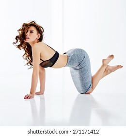 Lovely girl, curly hair, curled over his head, standing on his hands and knees, wearing a gray skirt and black bra, caved in back, on a white background, a little reflection on the floor