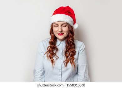 Lovely girl with curly hair and a red hat with a boumbon and red lipstick on her lips looks down and embarrassed on gray wall. Shopping, Sales, Giving Gift for Black Friday, Christmas and New Year
