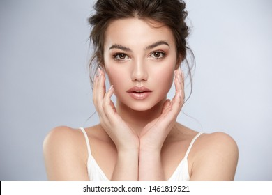 lovely girl with dark eyes and light make-up holding her arms near face, beauty portrait of caucasian white