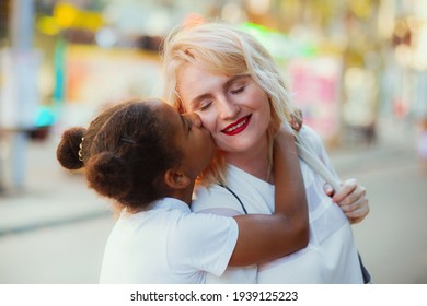 Lovely girl giving a kiss to her mother. Sweet family portrait