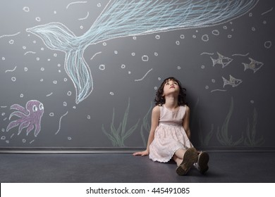 Lovely girl has an adventure to the world of sea. Big blue whale, violet octopus and fish depicted with chalk on the grey wall. Child sits on the floor and looks upwards.