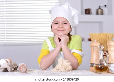 lovely girl in a hat chef knead the dough for the cake