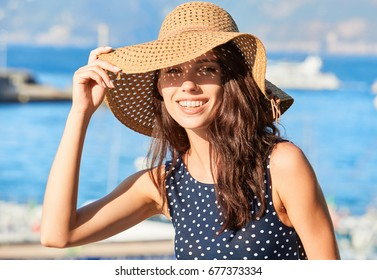 lovely girl in a hat protects her face from the sun