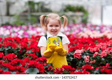 Lovely girl holding flowers in garden center.