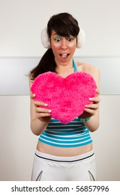 Lovely girl holding pink plush heart and acting surprised.
