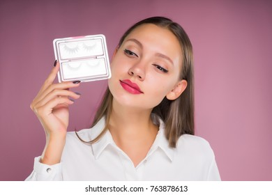 the lovely girl holds in the hands near the face a box with false eyelashes, and looked down, isolated on a pink background