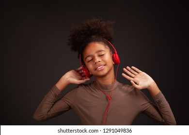 Lovely girl listening to music and dancing in red earphones against dark background