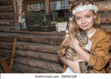 Lovely girl with the long blonde hair and blue eyes with the garland of white flowers on the wild west is a sweet grey kitten holding in his hand