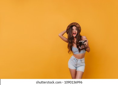 Lovely girl with long brown hair holding camera on yellow background. Studio shot of carefree female photographer wears hat and denim shorts.