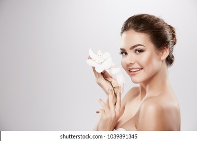 Lovely girl with nude make up and naked shoulders posing at grey background with flower, skin care concept, beauty photo, bio product.