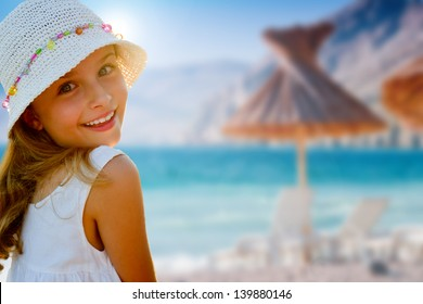 Lovely girl on tropical beach,beach chair and umbrella in background