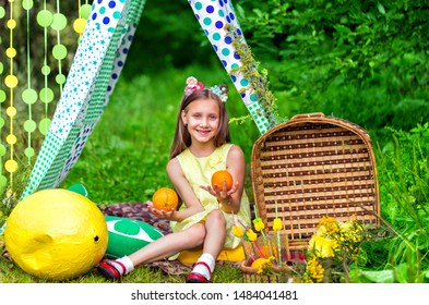 Lovely girl with picnic basket sitting in meadow in a tent
