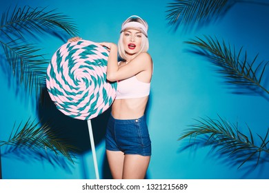 Lovely girl posing with huge lollypop and looking at camera. Beautiful blonde girl posing at blue studio background.