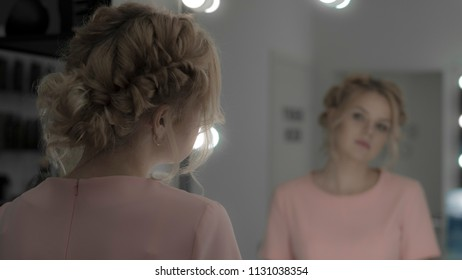 Lovely girl with professional hairstyle, makeup look at mirror in studio