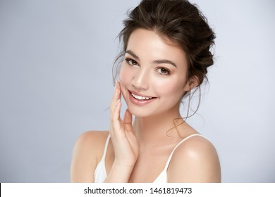 lovely girl with shiny smile and little curls touching her cheek and looking to camera, woman with light mua and perfect teeth