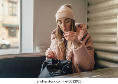 The lovely girl sits in cafe in the winter. On it a pink jacket and a cap. It gets white earphones from a black briefcase and tries to untangle them.