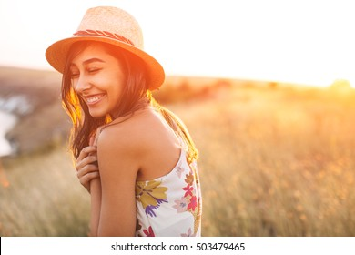 Lovely girl in stylish hat and summer dress smiling with closed eyes. Laughing young woman with sun light flare effect. Toned image