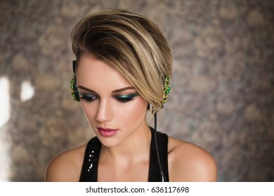 Lovely girl with tanned skin and white hair listening to music on headphones. Female beauty portrait of a beautiful makeup. Enjoying good music