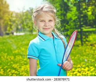 Lovely girl with tennis racket looking at camera in park
