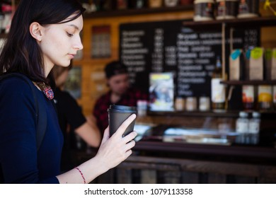lovely girl is thoughtfully holding a glass of coffee.