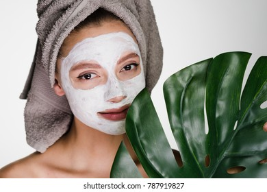 lovely girl with a towel on her head applied a white moisturizing mask on her face, a spa procedure