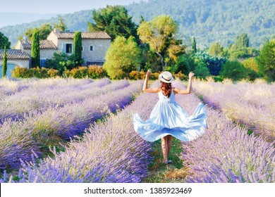 Lovely girl walking by blooming lavender fields in Luberon area in Provence, France. Beautiful girl dressing straw hat and blue boho chic dress - traditional Provencal style.
