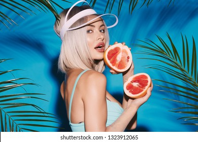 Lovely girl wearing blue swimwear and cap posing at studio background with palms, holding fruit and  looking at camera, eating fruit.