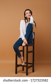 Lovely girl in white shirt and jeans sitting on tall wooden chair in studio