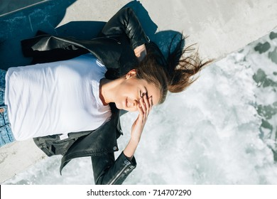 The lovely girl in a white t-shirt and a black leather jacket has lain down on a pier by the concerning sea. She covers eyes from bright beams of the sun and gently smiles.