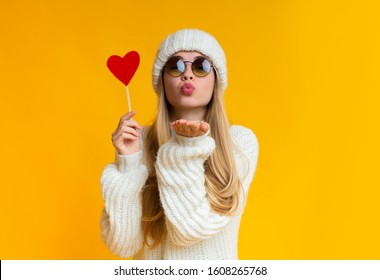 Lovely girl in winter hat and sunglasses holding red heart card and sending flying kiss, yellow background