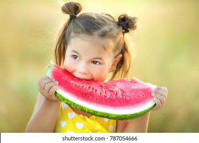 Lovely girl in a yellow bathing suit in a field eating a watermelon