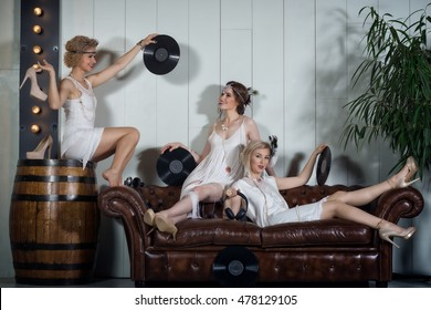 Lovely girls dressed in flapper style outfits have fun sitting on a leather sofa