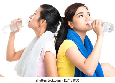 Lovely girls drinking water after intense workout
