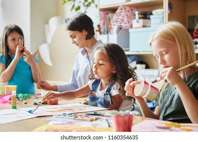 Lovely girls painting nice picture and painting cup while sitting in classroom near art teacher