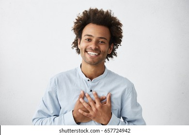Lovely good-natured Afro American man in white shirt having charming smile and friendly expression holding hands on heart wanting to show his love and sympathy to his girlfriend. My heart is for you!
