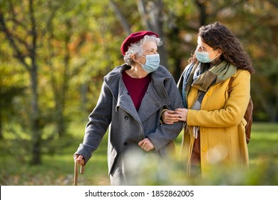 Lovely granddaughter walking with senior woman in park and wearing face mas against covid-19. Smiling old grandmother with happy caregiver in park relaxing after quarantine due to coronavirus.