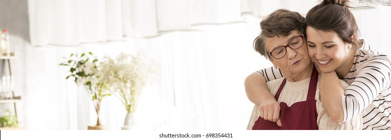 Lovely grandmother with beautiful, happy graddaughter in bright, cozy kitchen