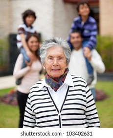 Lovely grandmother with her family outside their house